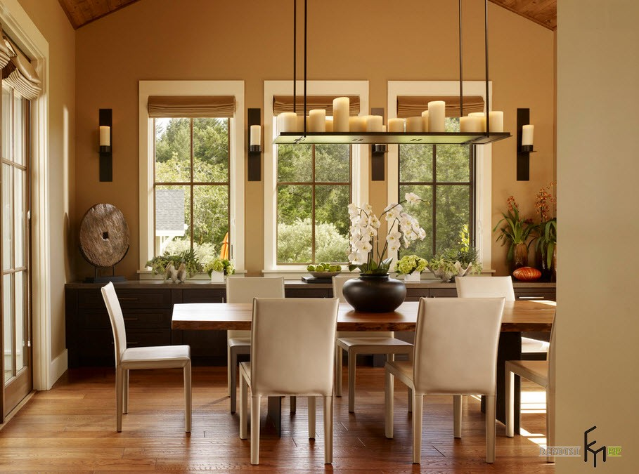 Candles and Candlesticks in the Modern Interior of Cozy Home. Brown colored dining room with the stand for candles instead of chandelier over the table