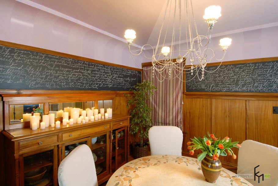 Candles and Candlesticks in the Modern Interior of Cozy Home. Unusual handwrite decoration of the upper part of the walls and wooden wainscoting