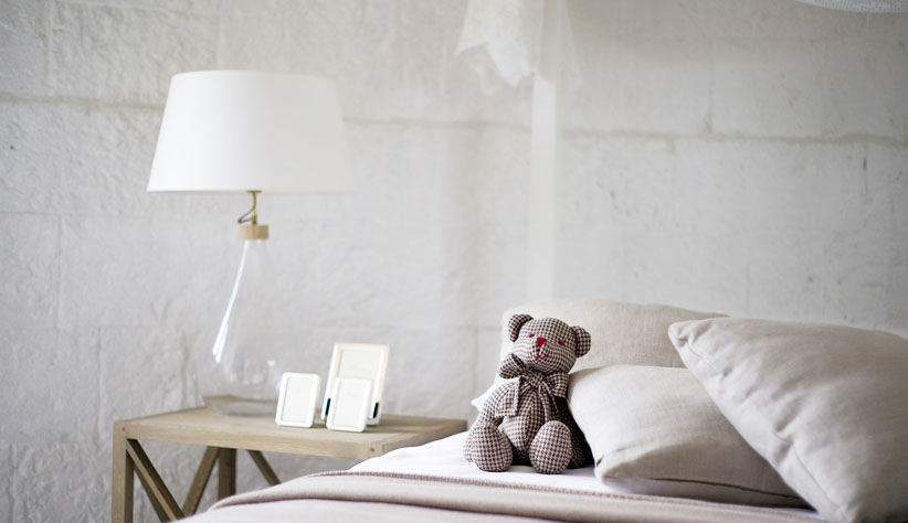 How To Make a Room Feel Bigger with Clever Lighting. Nice bedroom in white color with teddy bear at the bed