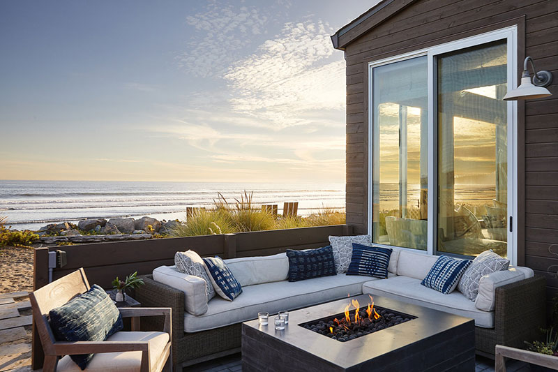 Backyard design with the view of the ocean and relaxing zone with the fire right at the table