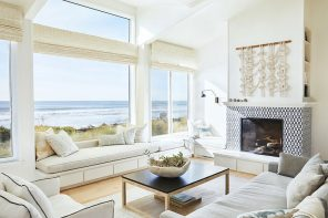 Cozy living room if the beach house with high ceiling and panoramic windows
