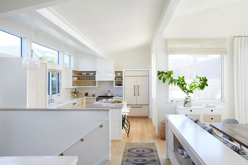 Sunny California Beach House Project in White. Light concise design of the large kitchen with plant as decoration