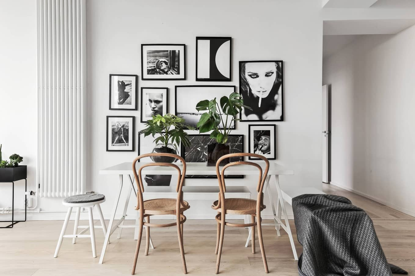 Nordic Interior Design Examples in Real Homes Photos. Black and white pictures and plants as the decoration for dining zone