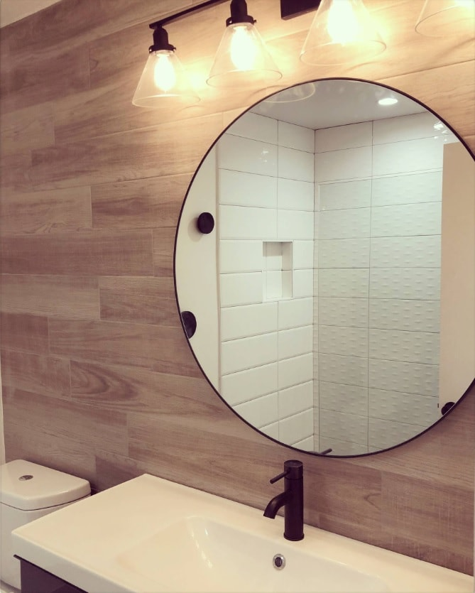 Chic round mirror in the Nordic styled bathroom with black tap