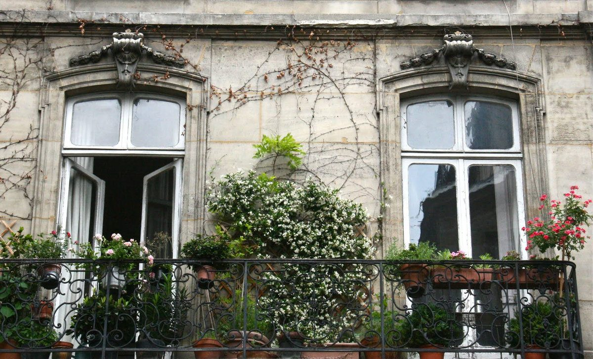 Classic exterior of the house with French balconies and plants
