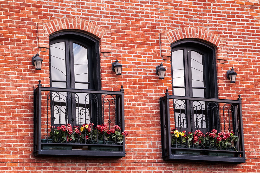 French Balcony in the Modern Interpretation and Decoration. Red facade brickwork