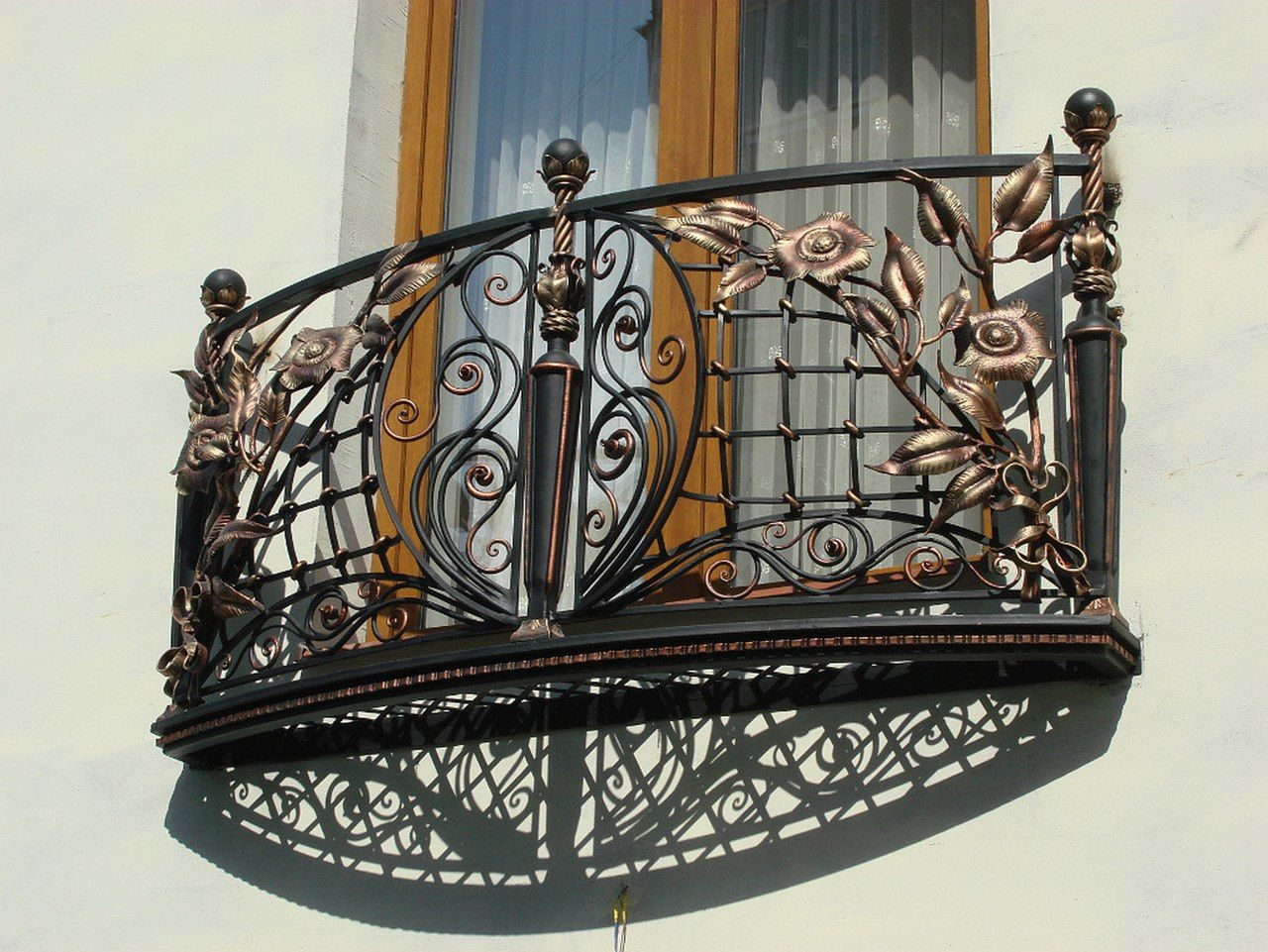 Unusual French Balcony design with forged fence and wood imitating window frame