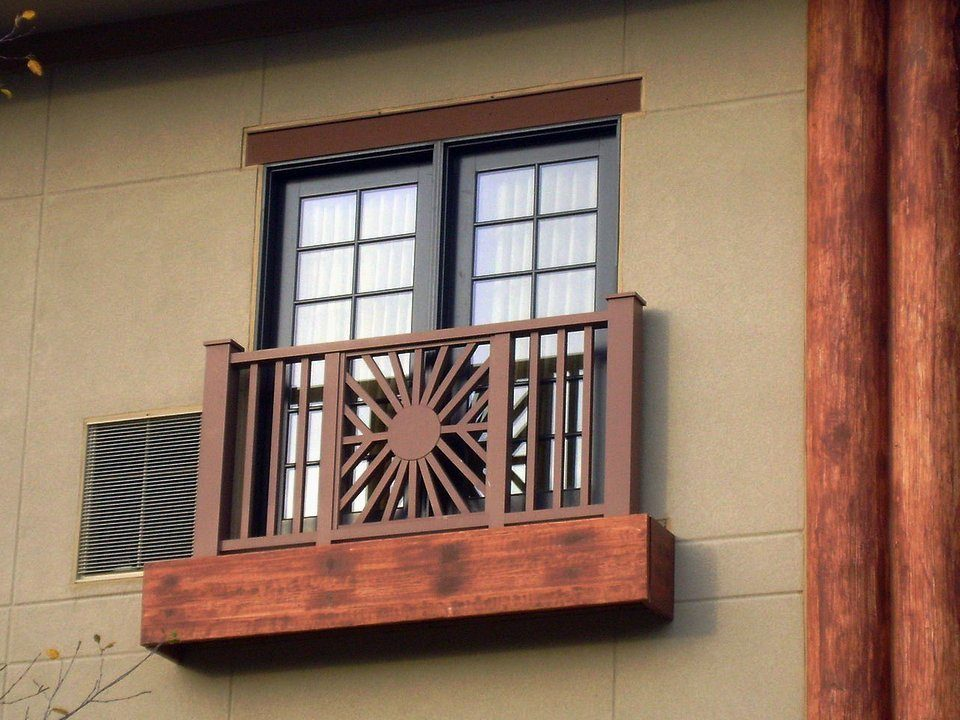 Sandy gray walls and wooden designed French balcony for classic exterior