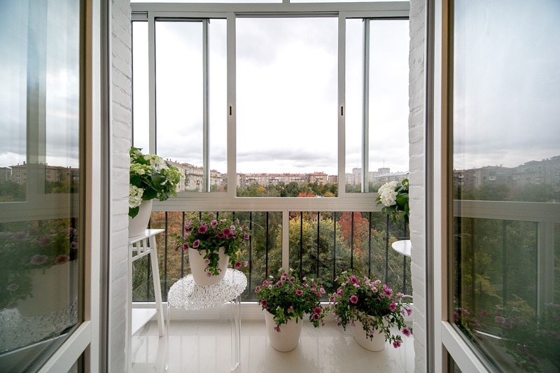 French Balcony in the Modern Interpretation and Decoration. Panoramic window in white and the wrought iron fence