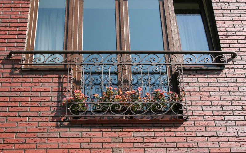 Nice contemporary styled facade of bricks and French balcony with flowers