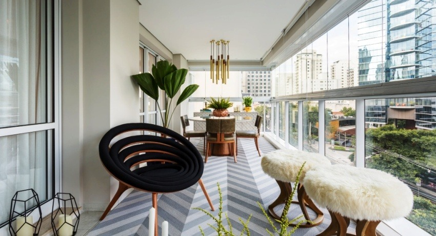 French Balcony in the Modern Interpretation and Decoration. Internal look at the large loggia with black relaxing chair