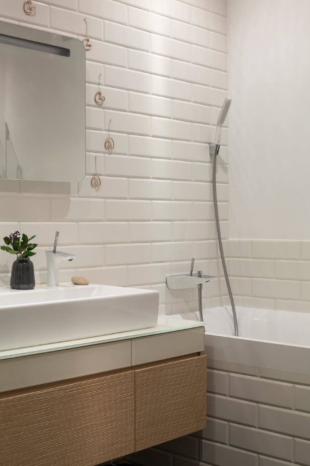 White brick imitating wall tiles and wooden facaded sink for the bathroom