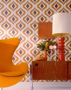 Reincarnation of Unrepeatable: 70s-80s Interior Design in Modern Interiors. Pattern on the wallpaper and yellow relaxing chair