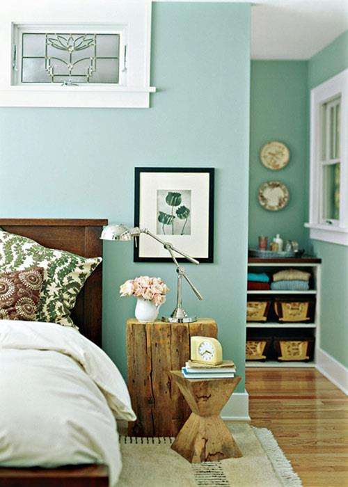 Green colored bedroom with wooden stand for the lamp