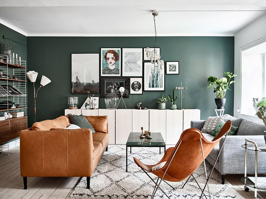 Dark green accent wall of the retro interior of the living room decorated with pictures