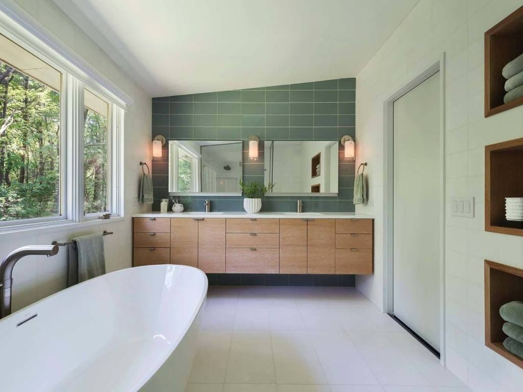 Green shallow tile for modern looking bathroom with large white stone bathtub