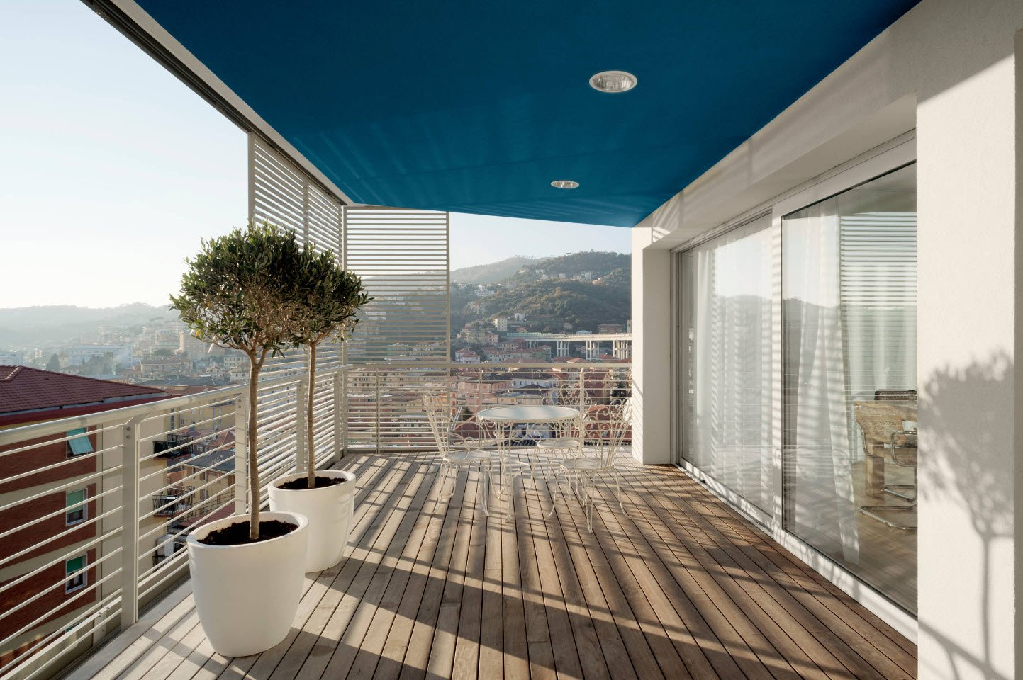 Gorgeous modern designed balcony with large pots for decorative trees and transparent delimeters