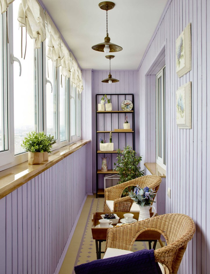 Purple striped loggia decoration with the sitting zone and wicker furniture