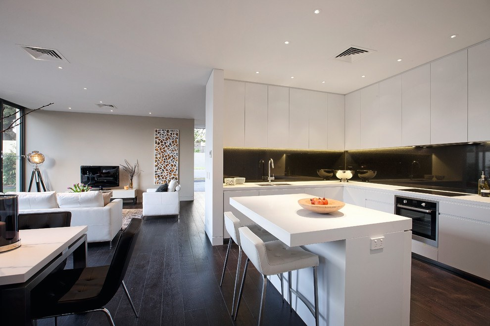 White kitchen with dark floor and dining zone at the island