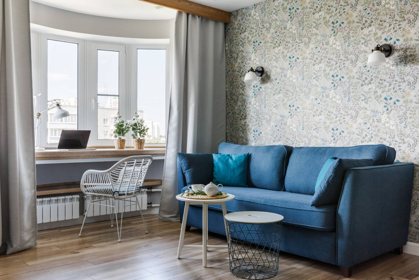 Large bay window balcony combined with the living room having blue sofa