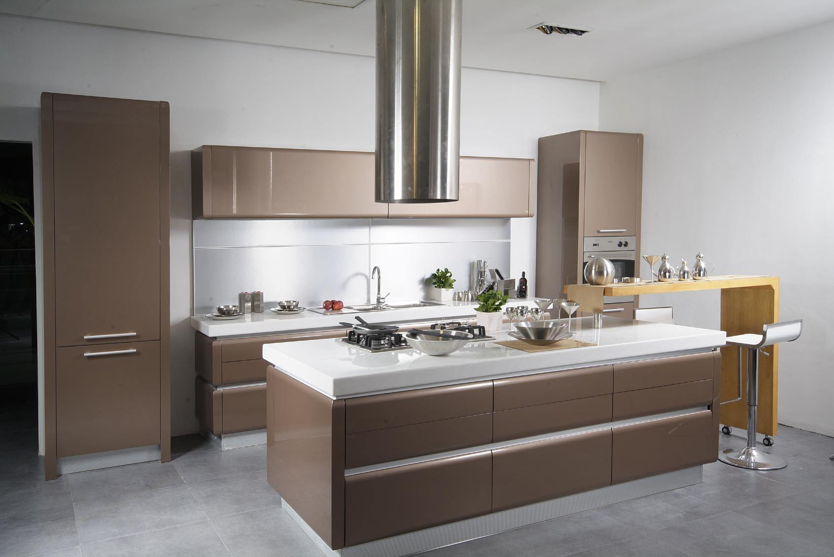 Coffee colored facades of the furniture set and tube-looking extractor hood avor the island