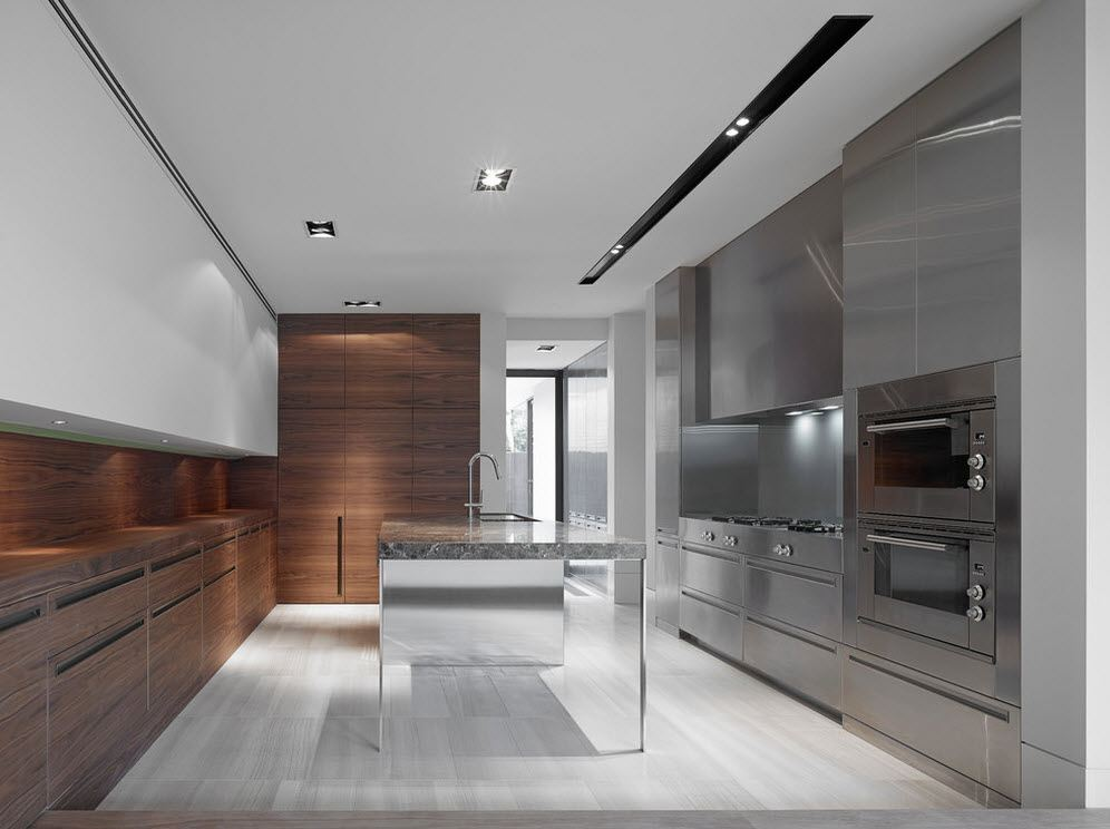 Gray designed steel surfaces of the kitchen furniture and wooden trimmed opposite wall