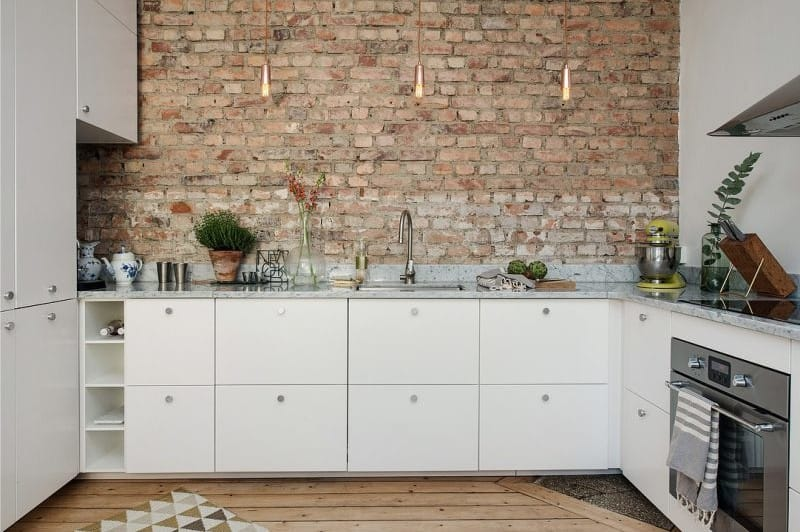 DIY Loft Style Interior Elements to Set Unrepeatable Atmosphere at Home. Open brickwork at the vintage kitchen with only bottom tier of white smooth furniture