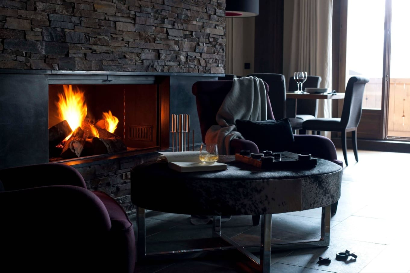 Chalet Style Interior Decoration: Relevance and Finishing Advice. Dark interior with the fireplace and cozy rugs