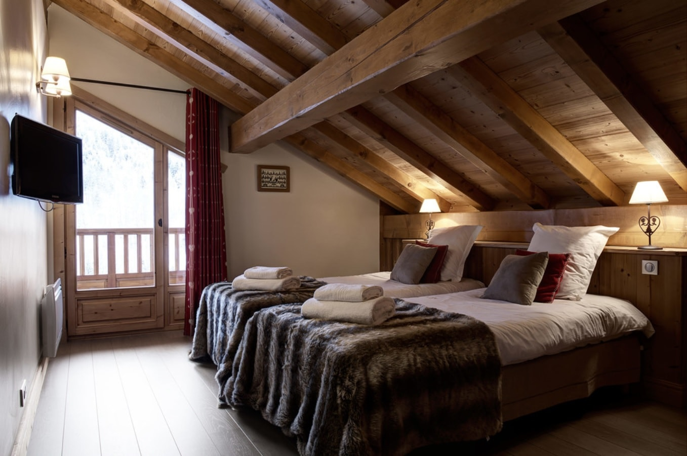 Loft wooden Chalet bedroom with two large beds and massive ceiling beams