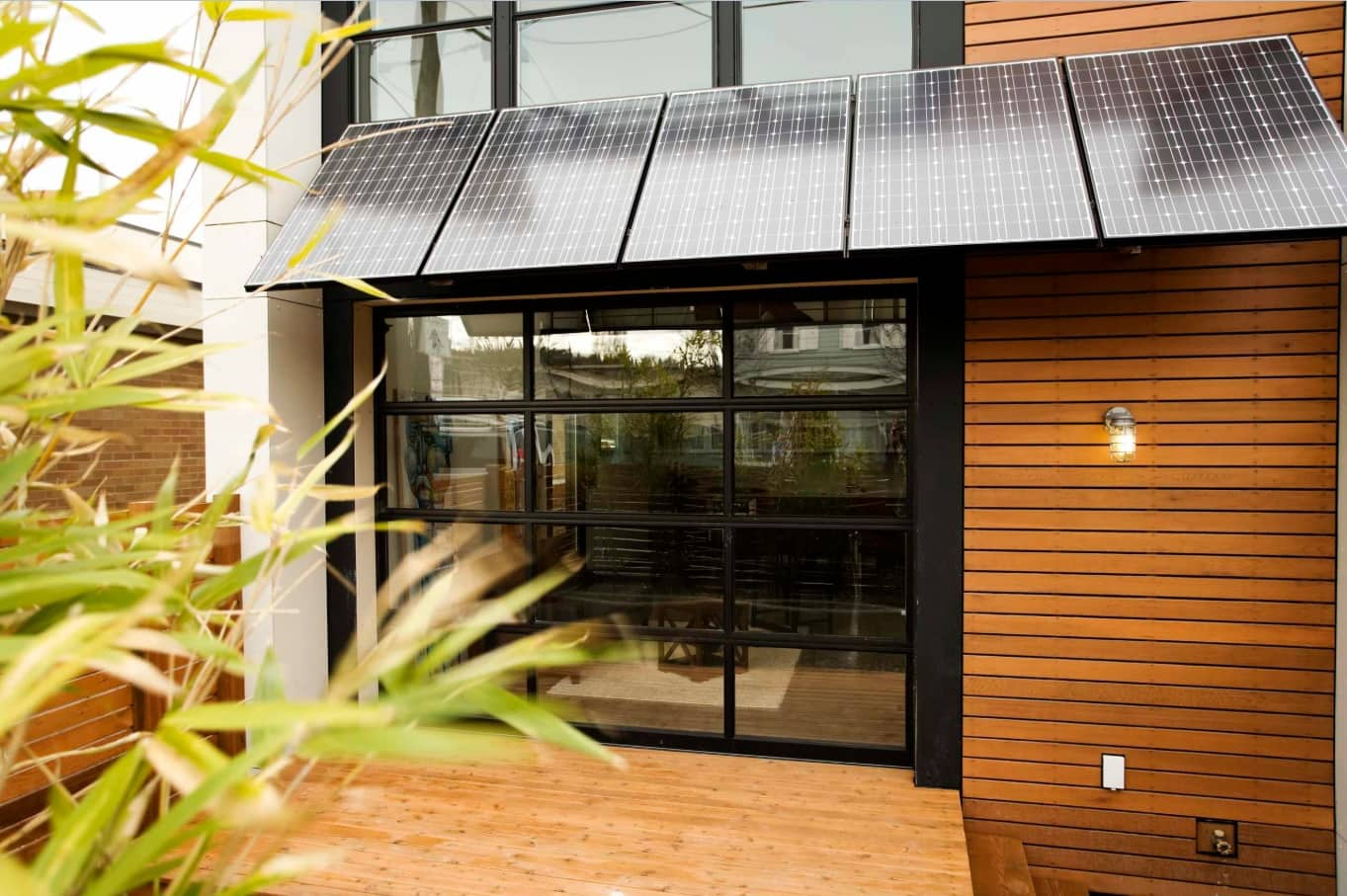 12 Ways You Could Make Your Home More Eco Friendly. Nice backyard of the modern wooden trimmed house with solar panels at the bulkhead