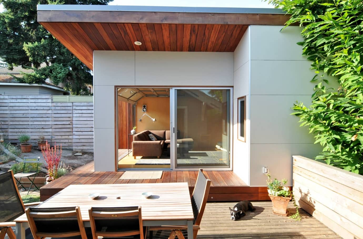 Sliding Glass Doors and Glass Wall Panels in Modern Commercial Interiors. Outside view if the backyard of the cottage with wooden platform outside the building