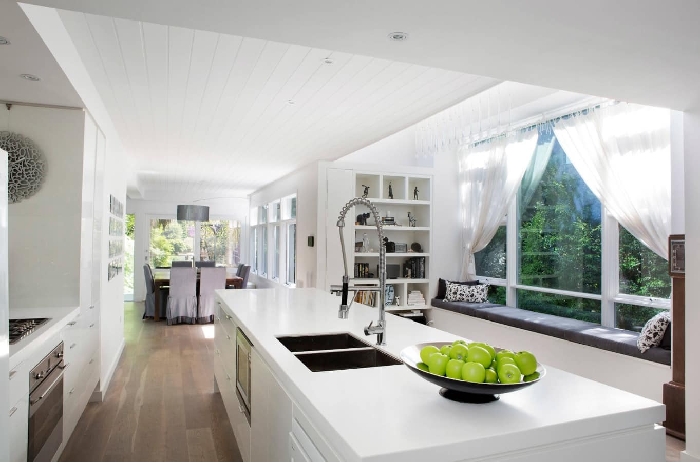 12 Ways You Could Make Your Home More Eco Friendly. White modern kitchen with large island and wooden laminated floor