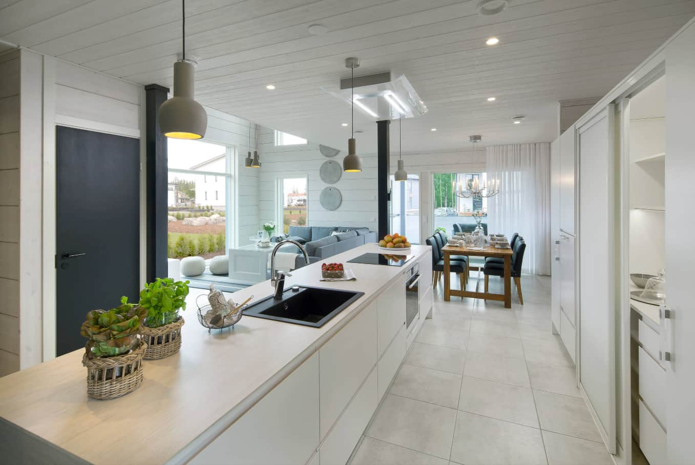 How to Redesign Your Kitchen This Summer. Absolutely white interior with the glossy surfaces and light tile, and very long island