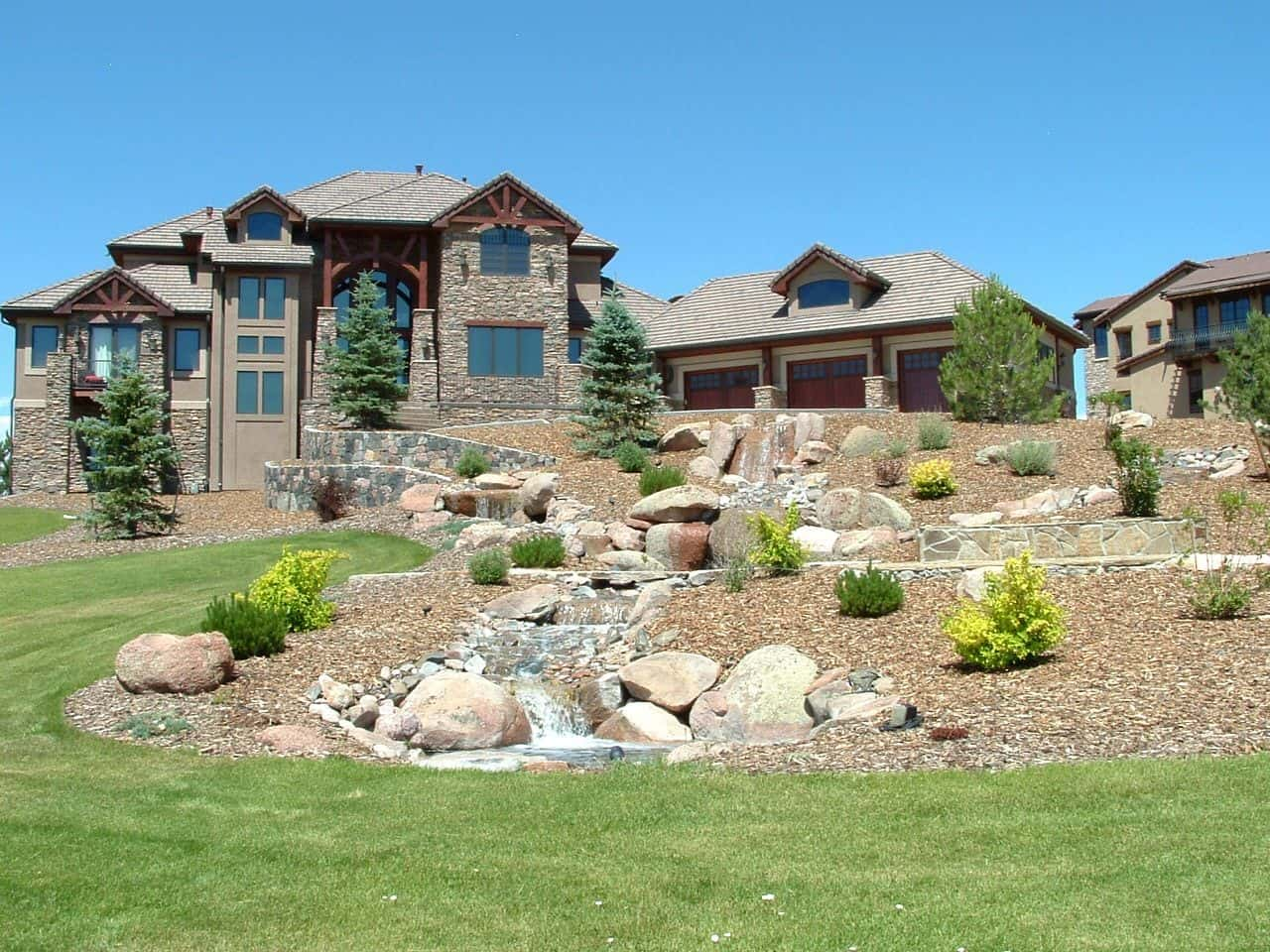 Stone facaded suburban mansion with successful slope landscape design at the front yard