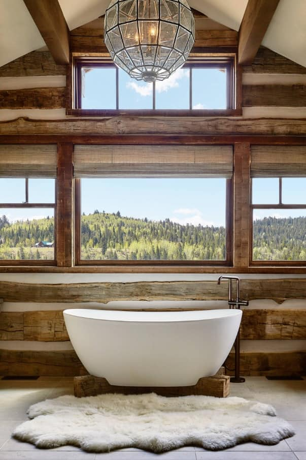 How to Turn Your Home Into a Dream Log Cabin. Gorgeous natural trimmed bathroom with central stone bathtub