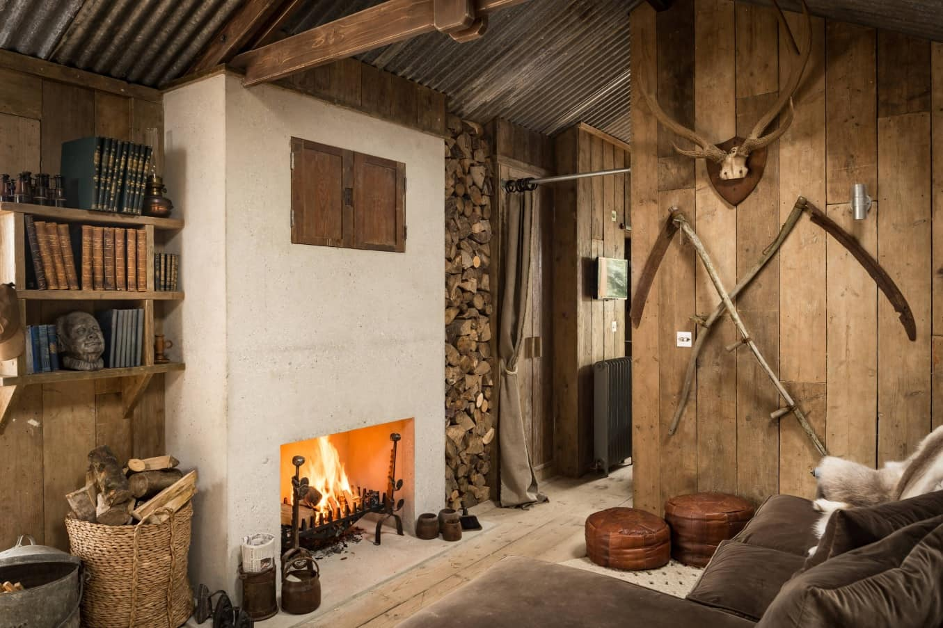 How to Turn Your Home Into a Dream Log Cabin. Fireplace and the firewood stock storage rack in the forester's house