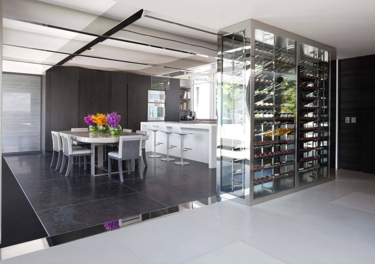 The Interior Design Guide For Styling a Gentleman's Elegant Man Cave. Kitchen zone on pedestal and glass casing for the wine shelving
