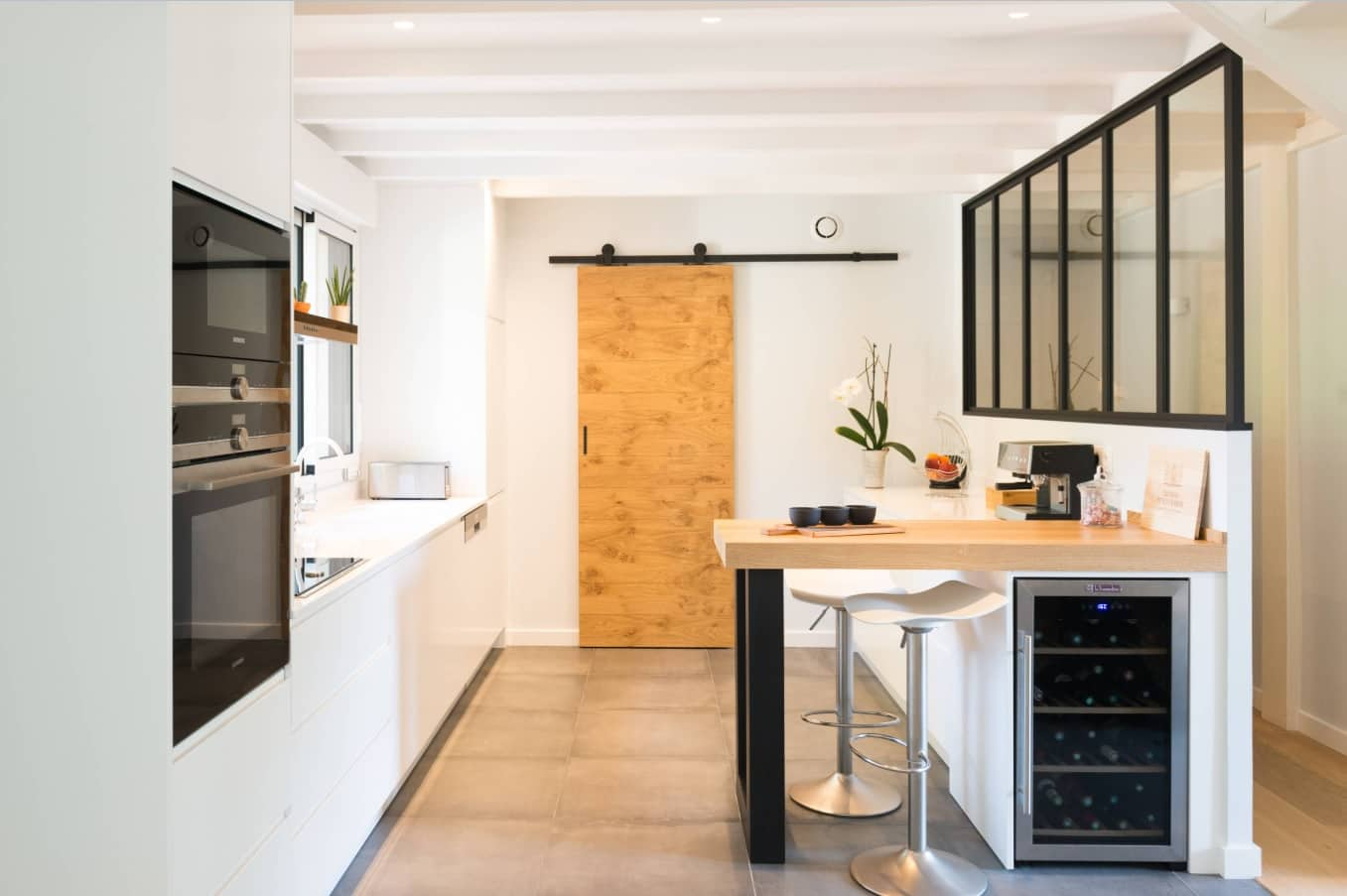 The Interior Design Guide For Styling a Gentleman's Elegant Man Cave. Sliding barn door and bar stand at the small kitchen