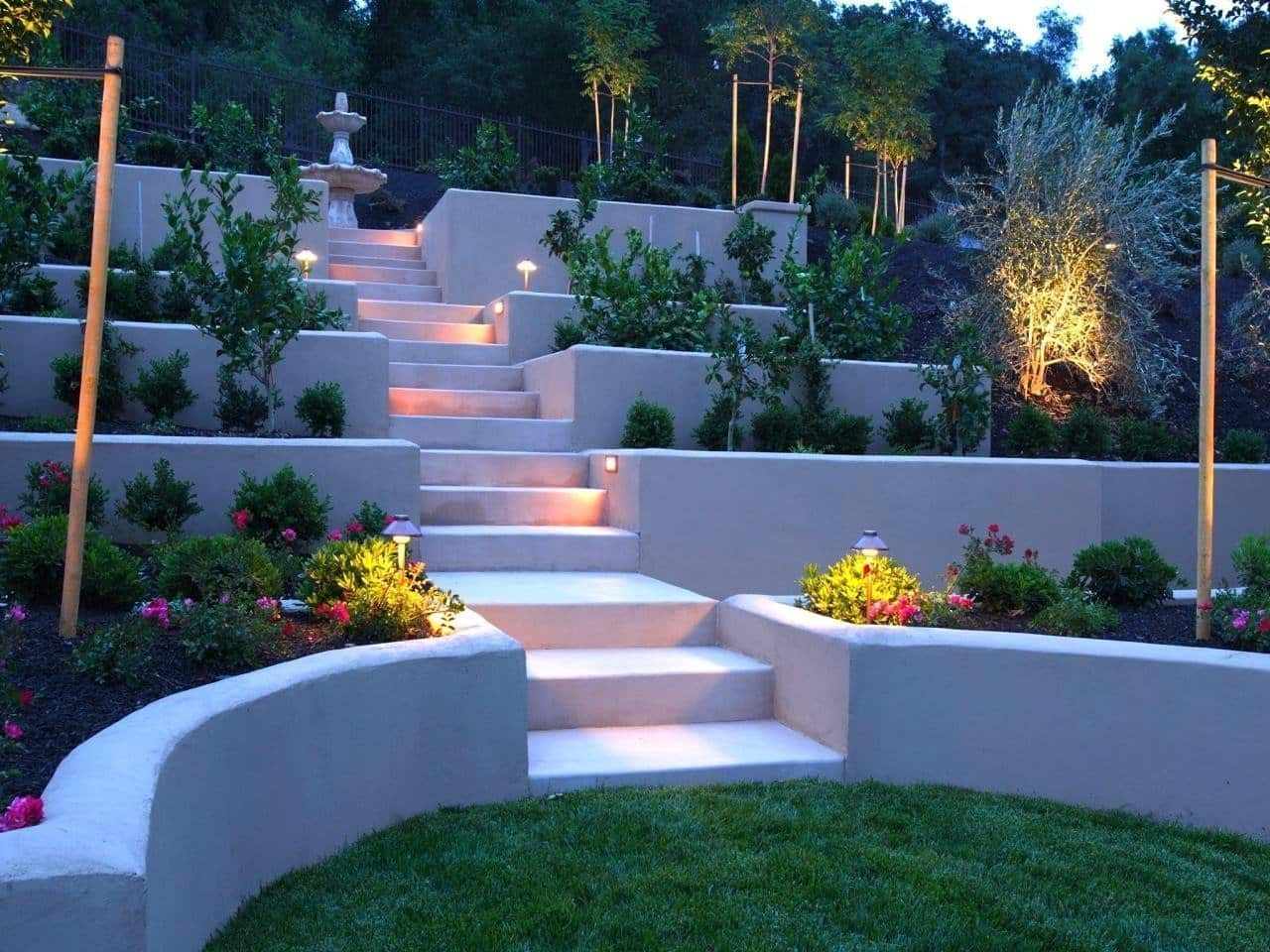 Great amphitheater looking backyard design with LED-lighting and white colored terraces