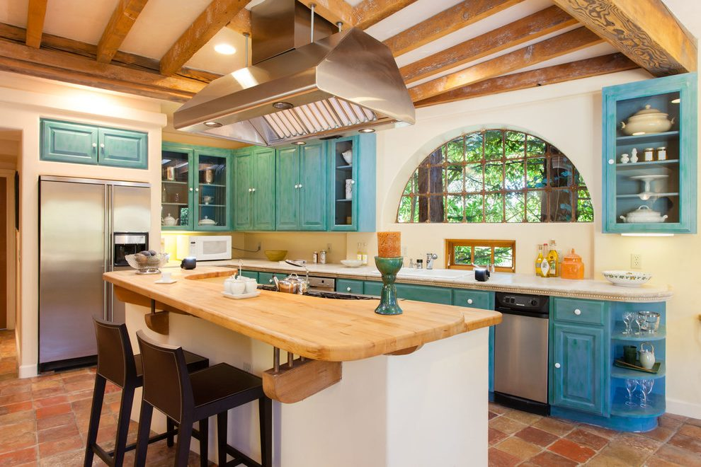 Rustic look of the kitchen with huge extractor hood over the wooden table