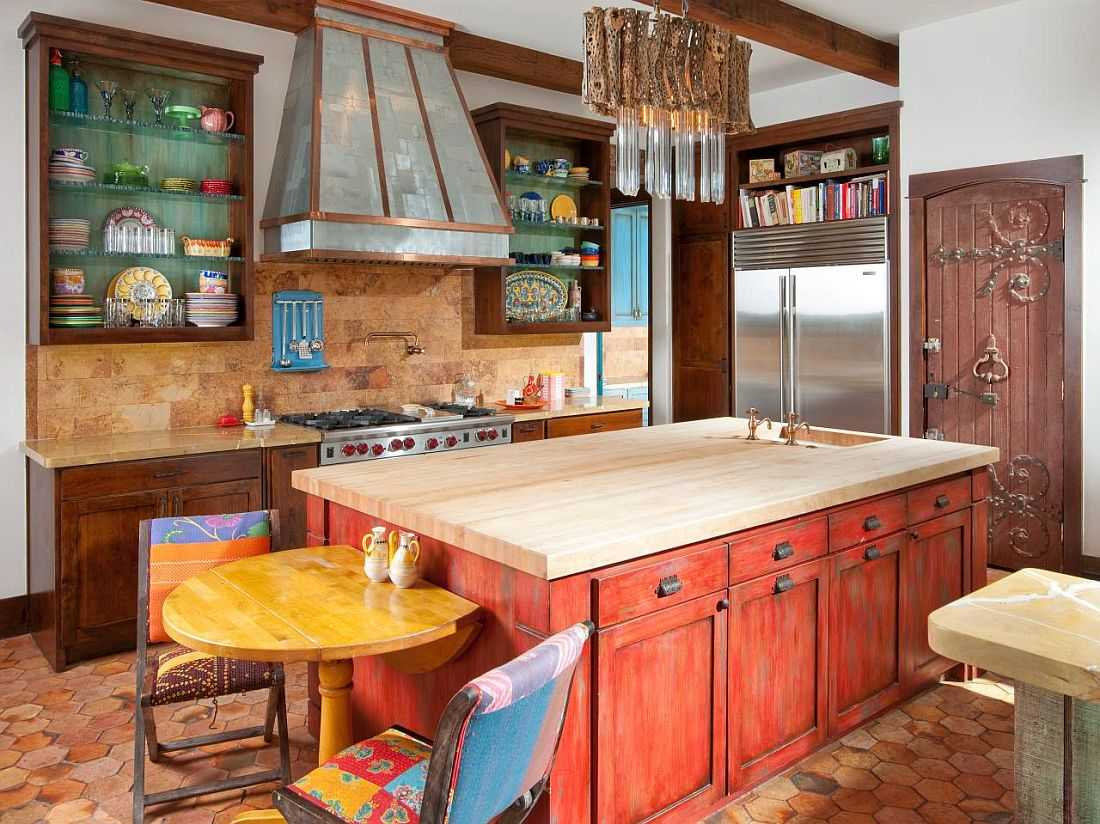 Bright red facades, steel fridge and blue painted extractor hood at the Mediterranean kitchen