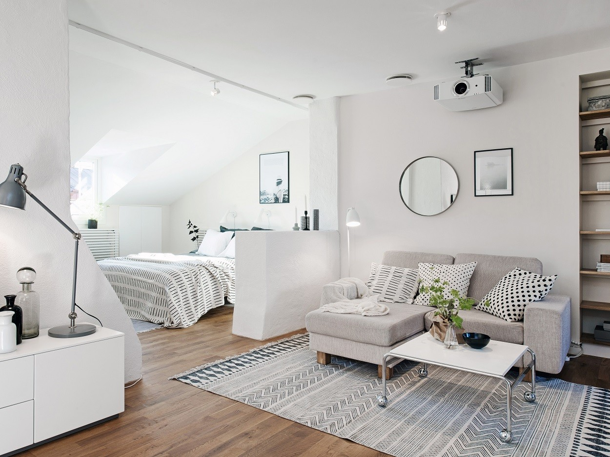 A couple of mirrors and wooden floor for the Scandi styled minimalist studio apartment with separated bedroom area