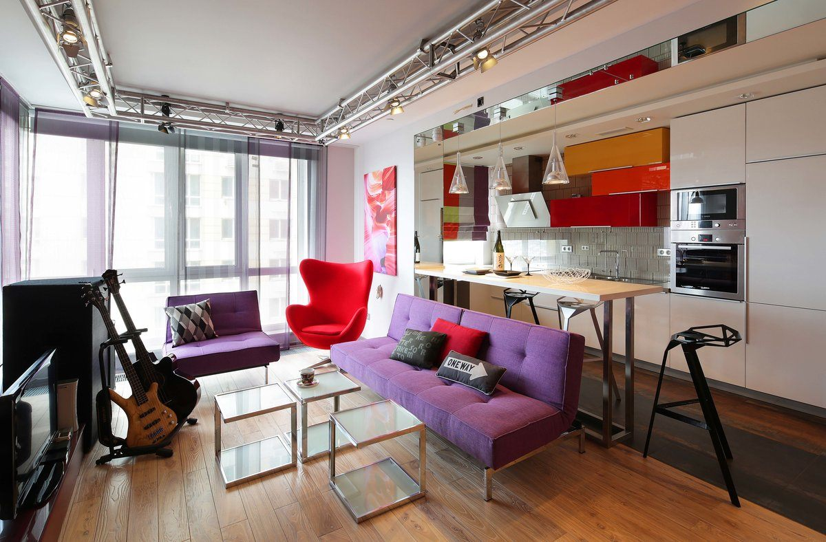 Purple sofas and screamy red chair to emphasize unusual fusion style in industrial premises