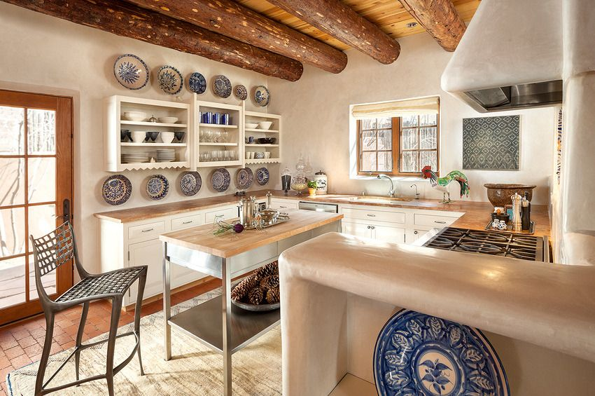 Painted blue dishes for decoration, steel butcher table and the apparent ceiling beams for Mediterranean kitchen