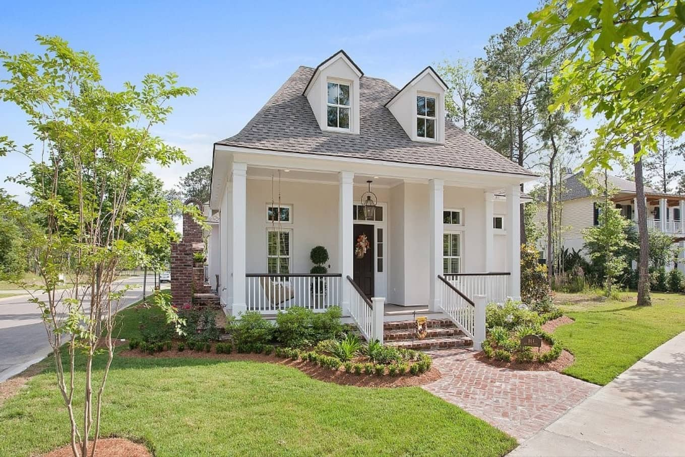 Acadian Style Home Design: Description, Floor Plans and Tips. Mid sized house in white with gray steep roof masterfully inscribedinto urban landscape