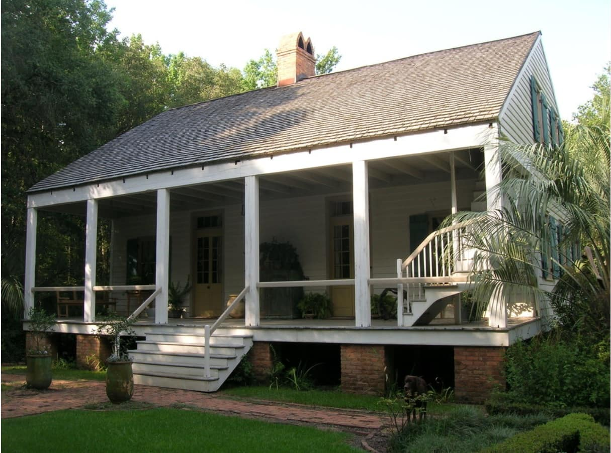 Acadian Style Home Design: Description, Floor Plans and Tips. Homey exterior with large deck leisure zone and the stairs to the upper level bedroom