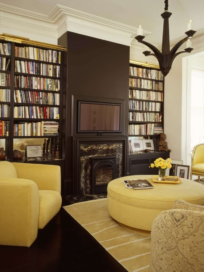 Cozy designed library with yellow toned furniture and central functional wall with built-in fireplace and TV-set