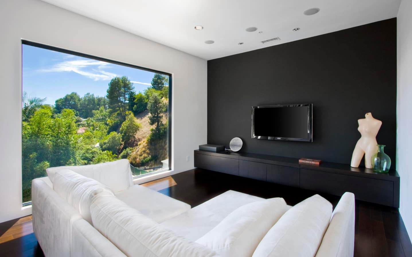 Breaking Stereotypes with Black Accent Wall Living Room Decoration. Panoramic window, black functional wall and white angular sofa for modern space