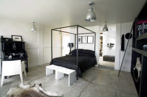 Bold, Unexpected, Mind-changing Industrial Studio Apartment Design. Canopy bed with black linen and white ottoman at the legboard in white room with metal pendant lamps