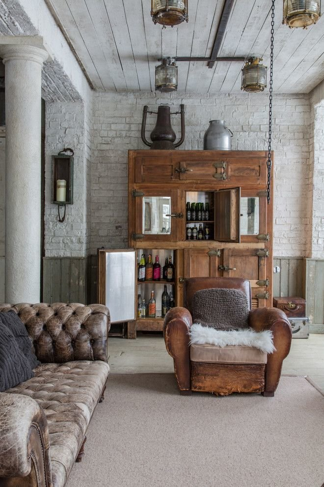 Bold, Unexpected, Mind-changing Industrial Studio Apartment Design. Old leather couch and armchair with pelt on the living zone of whitewashed high room